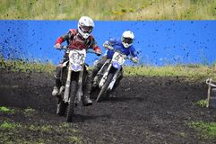 Racers on motorcycles participate in cross-country race competit Stock Photos