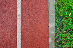 Racetrack with Grassfield. Bright-red racetrack with a vertical white line and fresh-green grass field Royalty Free Stock Images