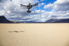 Racetrack Playa aerial patrol. A flying helicopter with raised landing gears and a camera flying over mesmerizing view of Racetrack Playa Stock Image