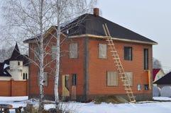 Rache-se em uma parede de tijolo de uma casa de campo inacabado dois-storeyed. Imagem de Stock Royalty Free