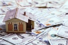 100 rachunków pojęcia dolara dom robić hipotekuje robić pieniądze w domu Miniaturowy domu model na stosie Obrazy Stock