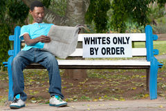 Racial discrimination. A non-white man sits on a bench in a park reserved for whites. This was commonplace during the apartheid years in South Africa Stock Photo