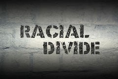 Racial divide GR. Racial divide stencil print on the grunge white brick wall royalty free stock photography