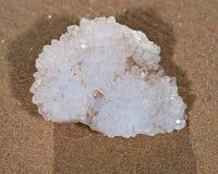 Racimo de Aurora Rainbow Quartz de la India que está situada en la arena mojada en la playa Foto de archivo