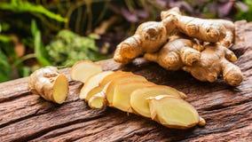 Racine de gingembre - racine fraîche de gingembre et découpé en tranches sur la vieille planche avec le fond de nature Photographie stock