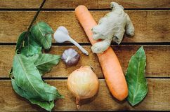 Racines ail, oignon, carotte, feuille de laurier se trouvant sur une table en bois photos libres de droits