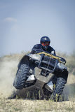 Racing atv is sand. A man riding ATV in sand in protective clothing and a helmet Royalty Free Stock Photos