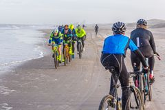 Racing bike competition riders in beach. Kijkduin, The Hague, the Netherlands - 28  January 2018: Beach racing bike competition riders in beach race in The Hague Royalty Free Stock Photos