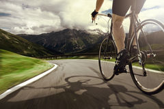 Racing Bike. Racing Cyclist rides downhill in a mountain landscape Stock Images