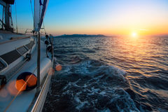Racing on a boats in the wind on the waves of the sea during amazing sunset. Luxury sailing yachts in the regatta Stock Images