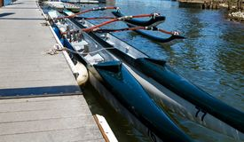 Racing Canoes at the Dock on the River royalty free stock image