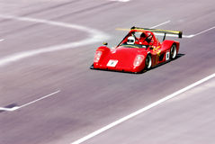 Racing car. A red racing car in action at the track, motion blur Stock Image
