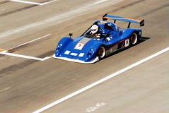 Racing car. A blue racing car in action at the track, motion blur Royalty Free Stock Photo