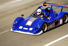 Racing car. A blue racing car in action at the track, motion blur Stock Photo