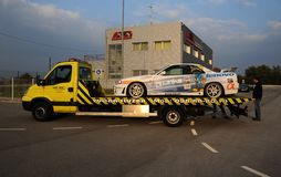 Racing car being transported on a truck in sunset Royalty Free Stock Photography