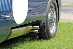 Racing car exhaust and spoke wheel. Photo of a british racing car showing chrome exhaust and spoke wheel Stock Photo