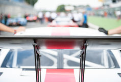 Racing car rear spoiler detail. Racing car black rear spoiler detail with blurred cars and mechanics in background on starting grid line Stock Images