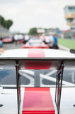 Racing car rear spoiler detail. Racing car black rear spoiler detail with blurred cars and mechanics in background on starting grid line Stock Image