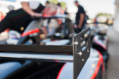 Racing car rear spoiler detail. Racing car black rear spoiler detail with out of focus starting grid in background Royalty Free Stock Images