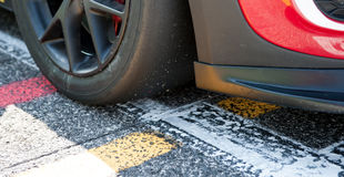 Racing car tire detail on asphalt starting line. Racing car tire detail on asphalt speedway starting line, red and black Royalty Free Stock Images