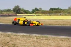 Racing car. Yellow racing car on the track royalty free stock photos