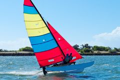 Racing Cat sailing with Blue Sky. Sailing cat competing in race on the Burnett River Bundaberg staged by the Bundaberg Sailing Club. Queensland - Australia Royalty Free Stock Images