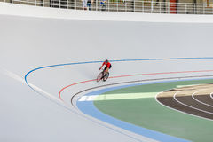Racing cyclist on velodrome outdoor. Professional athlete in a red T-shirt and a black bicycle Royalty Free Stock Image