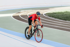 Racing cyclist on velodrome outdoor. Professional athlete in a red T-shirt and a black bicycle Stock Images