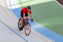 Racing cyclist on velodrome outdoor. Professional athlete in a red T-shirt and a black bicycle Royalty Free Stock Photography