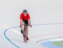 Racing cyclist on velodrome outdoor. Professional athlete in a red T-shirt and a black bicycle Royalty Free Stock Images