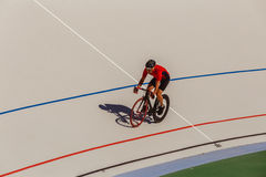 Racing cyclist on velodrome outdoor. Professional athlete in a red T-shirt and a black bicycle Royalty Free Stock Photo