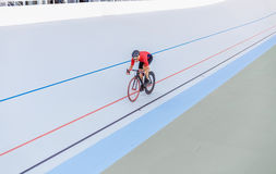 Racing cyclist on velodrome outdoor. Professional athlete in a red T-shirt and a black bicycle Stock Photography