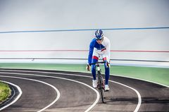 Racing cyclist on velodrome outdoor. Young professional cyclist on a velodrome Stock Image
