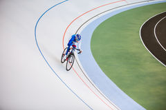 Racing cyclist on velodrome outdoor. Young professional cyclist on a velodrome Royalty Free Stock Photography