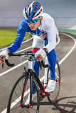 Racing cyclist on velodrome outdoor. Young professional cyclist on a velodrome Royalty Free Stock Photos