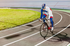 Racing cyclist on velodrome outdoor. Young professional cyclist on a velodrome Stock Photo