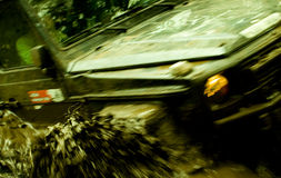 Racing in dirt. A blur image of a special heavy terrain vehicle racing through wet mud Stock Photos