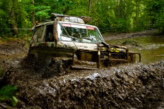 Racing in the Dirt. Special vehicle meant for racing in heavy terrain conditions stuck a stream with lots of mud, on a dirt race track stock photo