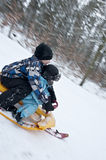 Racing downhills on  a snow sledge. Two young boys going downhills on a modern snow sledge Royalty Free Stock Images