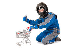 Racing driver shopping. Racing driver posing with shopping cart isolated in white Royalty Free Stock Photo
