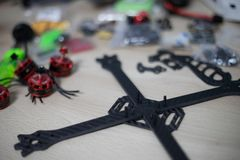 Racing drone frame being mounted on wooden table with blurred tools on background stock photo