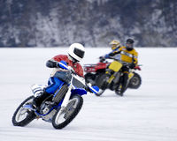 Racing on Ice. Motorcycle in the lead racing against another cycle and a 4-wheeler on a frozen lake Royalty Free Stock Photo