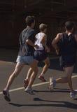 Racing men. Three running men on the street Stock Image
