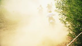 Racing on motorcycles, jumping on a dusty road stock video