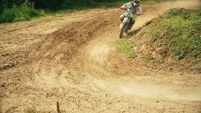Racing on motorcycles, jumping on a dusty road stock footage