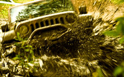 Racing Through Mud. A blur image of a special heavy terrain vehicle racing through wet mud Royalty Free Stock Photo