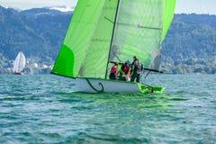 Racing sailboat with green spinnaker sailing a regatta at lake c photographie stock