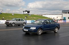 Racing saloon cars. PODINGTON, UK - APRIL 11: An unnamed driver takes his modified Volkswagen Golf VR6 automobile for a timed run down the Santa Pod raceway at Royalty Free Stock Photos