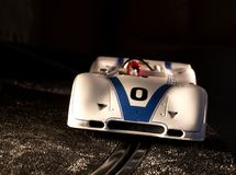 Racing the slot. White slot car that is making a right handed corner Royalty Free Stock Photos