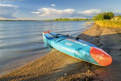 Racing stand up paddleboard on lake shore. Loveland, CO, USA - June 24, 2018: A racing stand up paddleboard by Starboard with a paddle and safety leash on a stock image